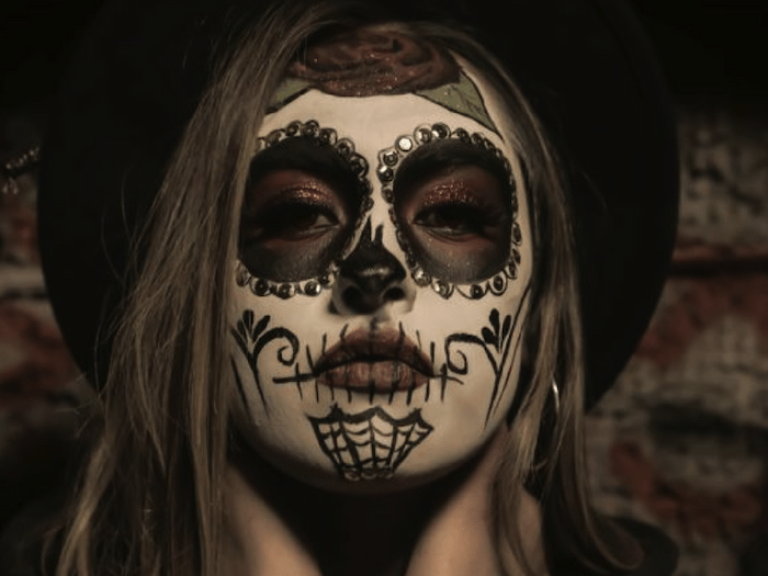woman with black hat, calavera make up, halloween costume ideas for women, brown hair