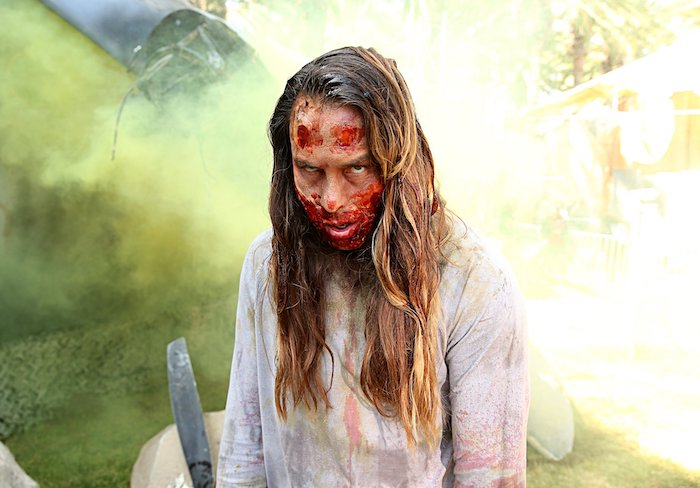 woman dressed as a zombie, white torn shirt, bloody face make up, halloween costume ideas for women, brown hair
