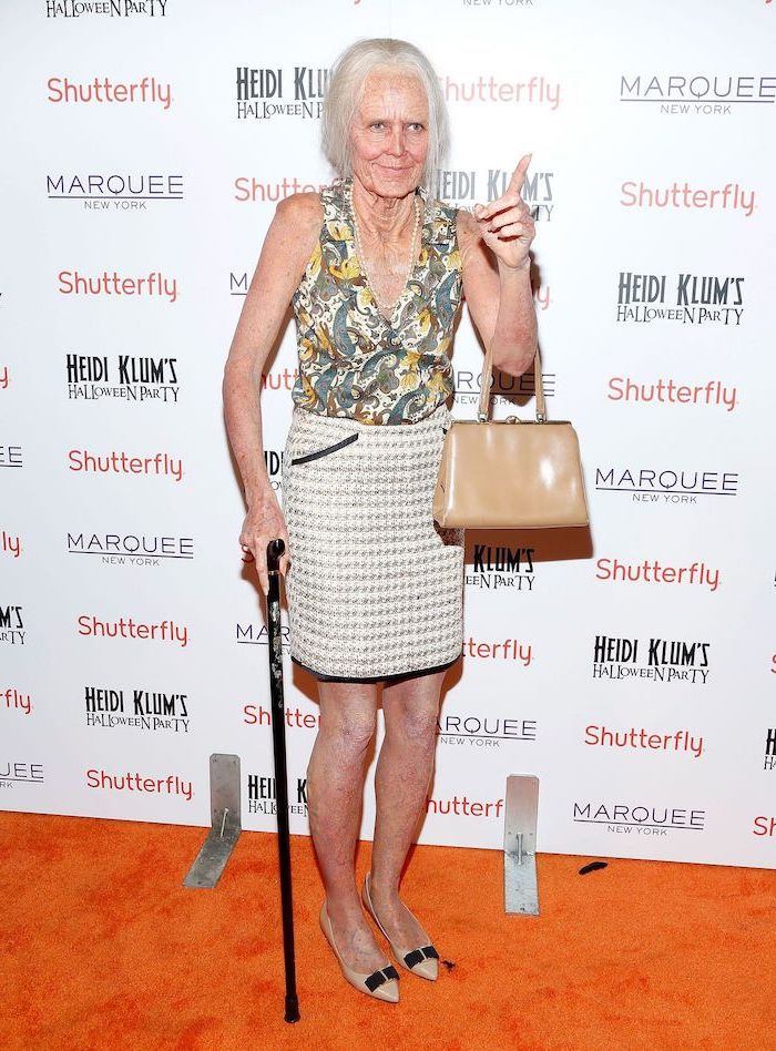 heidi klum, dressed as an old woman, full body make up, simple halloween costumes, holding a cane