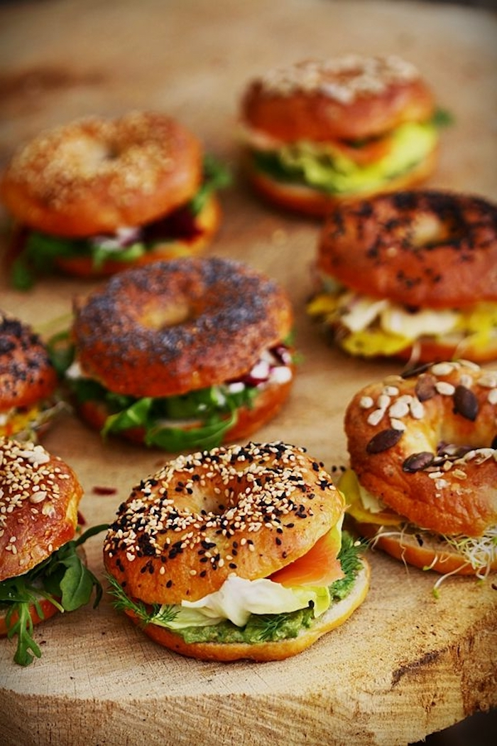 halved bagels, with spinach, salmon and cheese, breakfast potluck, wooden board
