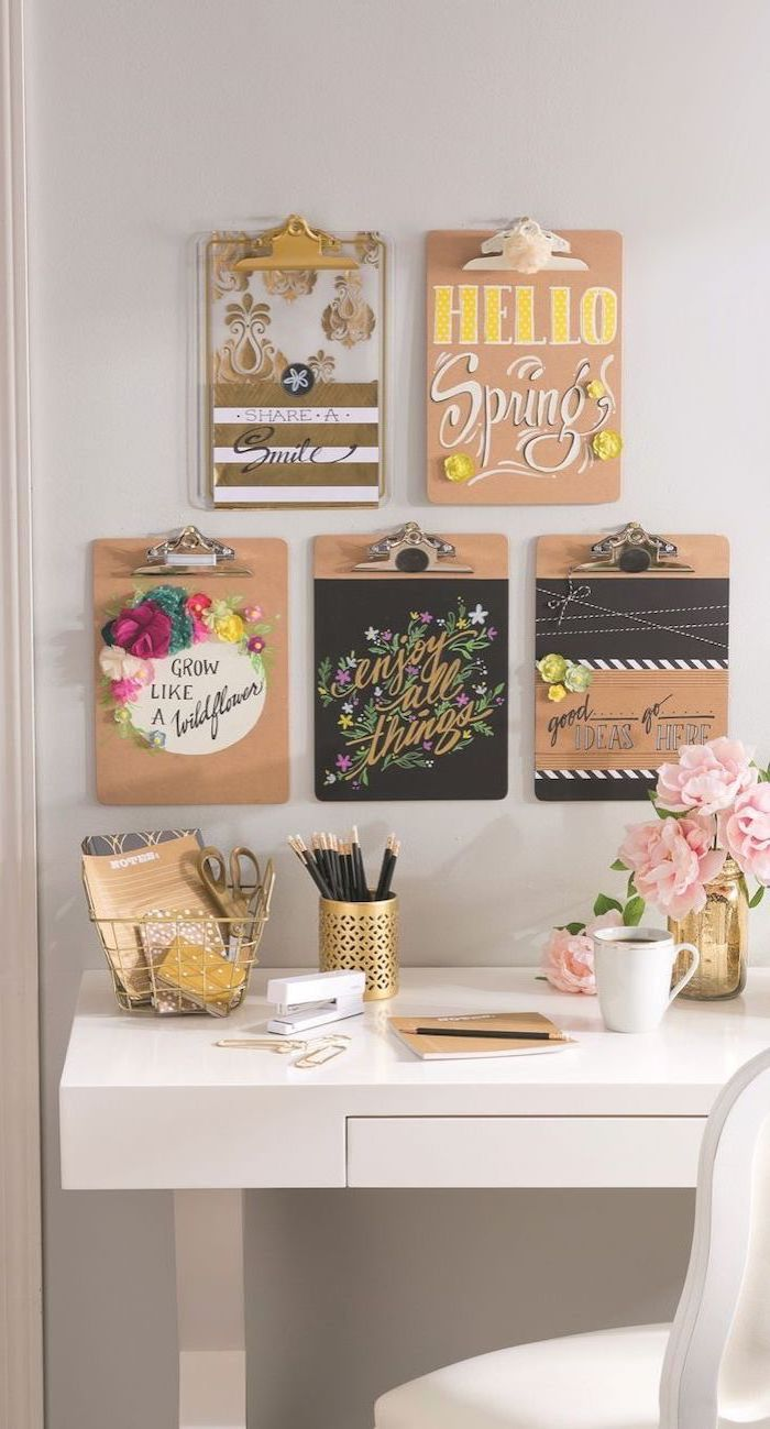 hanging folders, on a white wall, different inspirational quotes, white desk, gold desk accessories, cute office decor
