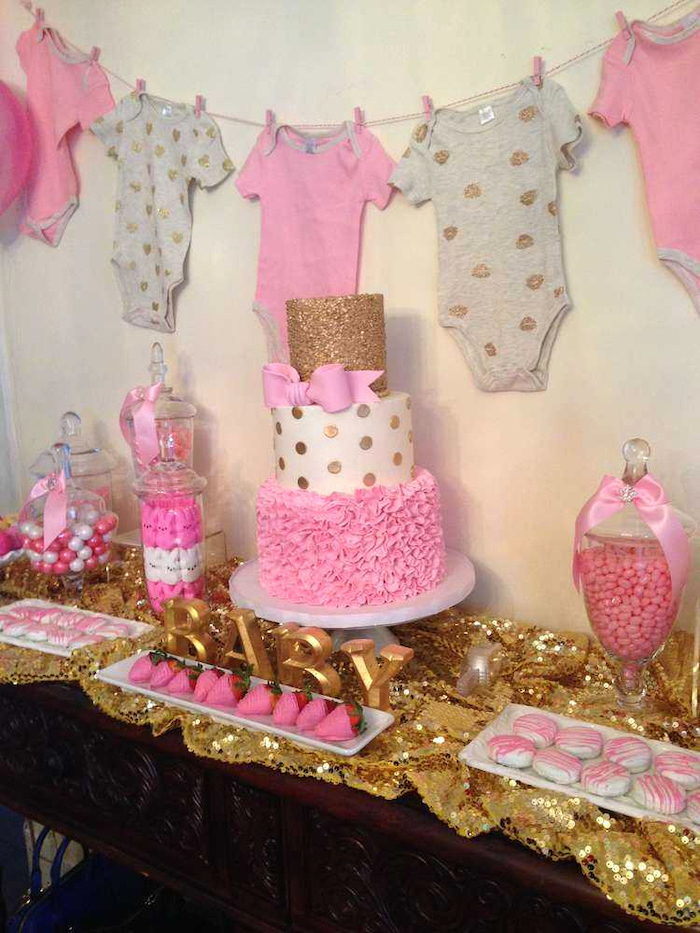 hanging pink and grey onesies, three tier cake, cookies and strawberries, when to have a baby shower, candy jars