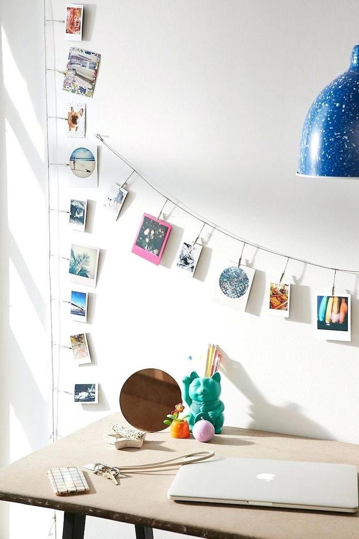photos hanging on a string, above a wooden desk, cute office decor, keys phone and laptop, white wall