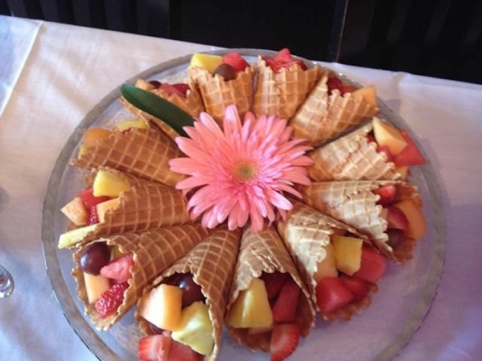 ice cream cones, filled with fruit, brunch items, strawberries and grape, pineapple and melon
