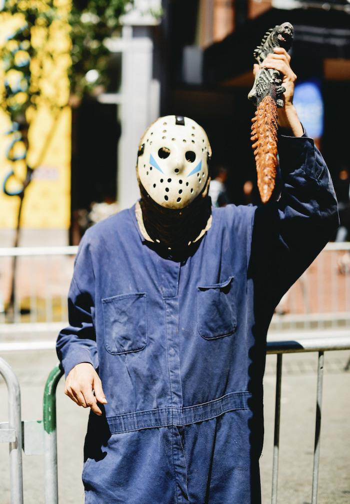 man dressed as jason voorhees, simple halloween costumes, blue onesie, holding a weapon, hockey mask