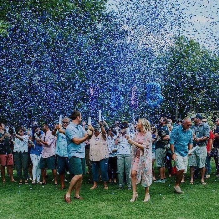gender reveal decorations, lots of people smiling, standing on a field, blue confetti in the air