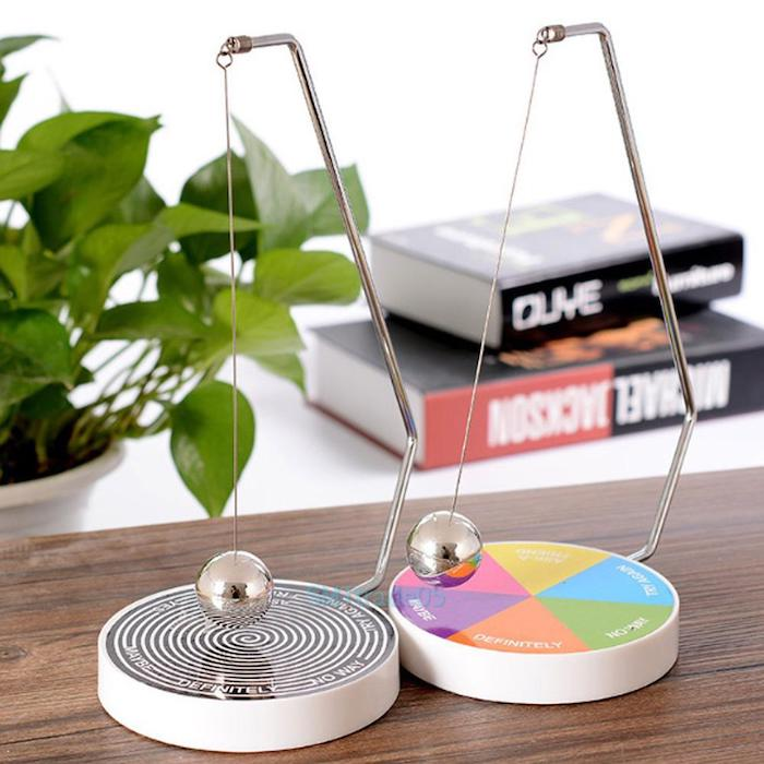 magnetic decision making balls, on a wooden desk, office decor ideas for work, potted plant, two books