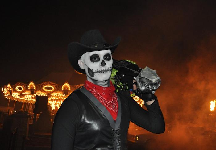 man with a chainsaw, skeleton face makeup, wearing a hat, red bandana, black leather vest, easy halloween costumes
