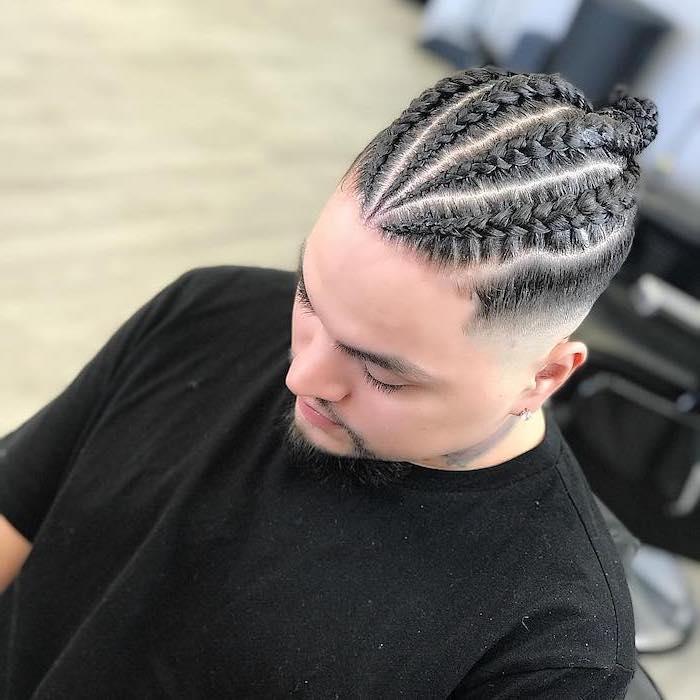 man with black hair, braided in a bun, wearing a black t shirt, asap rocky braids