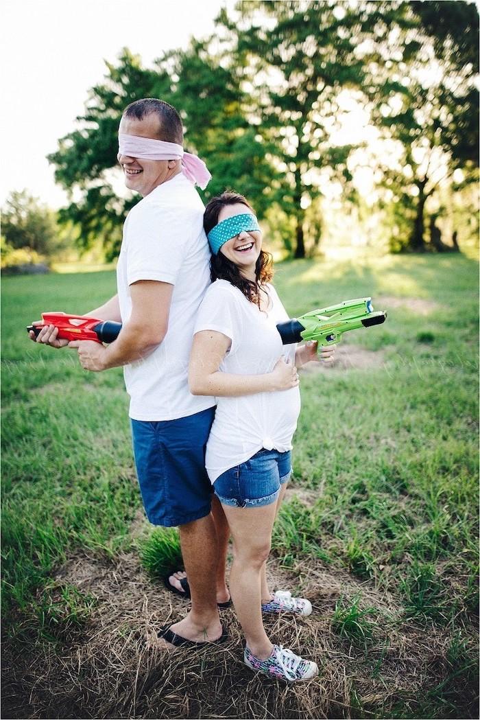 man and woman, standing back to back, gender reveal party, golding nerf guns, wearing blindfolds