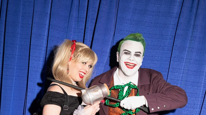 the joker and harley quinn, creative halloween costumes, man and woman smiling, standing in front of a blue curtain