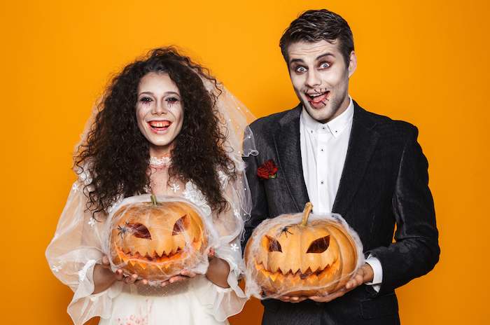 man and woman smiling, holding pumpkins, dressed as bride and groom, diy halloween costumes, orange background