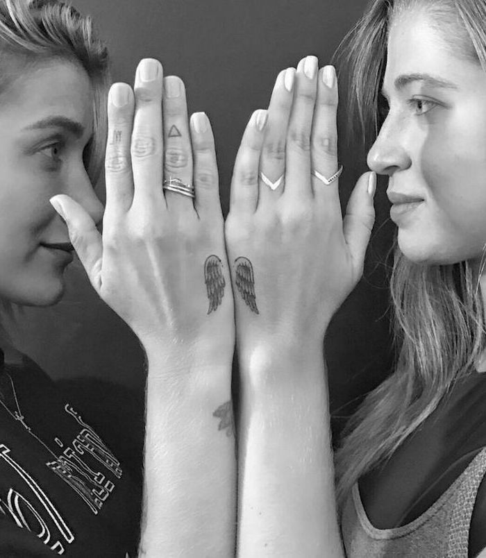matching sister tattoos, hand tattoos, angel sleeve tattoo, two women, facing each other, silver rings