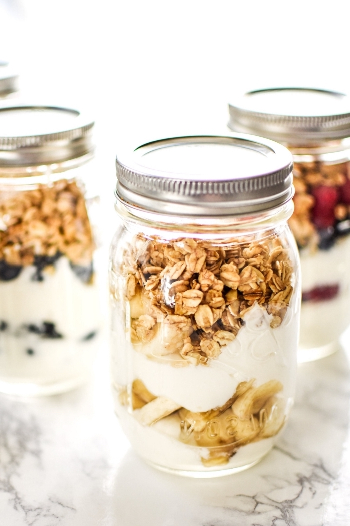yoghurt and granola, inside a mason jar, brunch potluck ideas, chopped banana, strawberries and blueberries