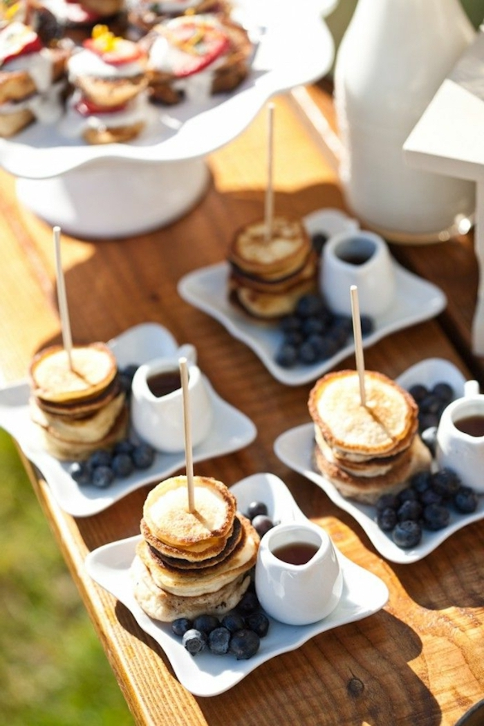 stacks of mini pancakes, blueberries on the side, easy brunch ideas, honey in a jug, wooden table