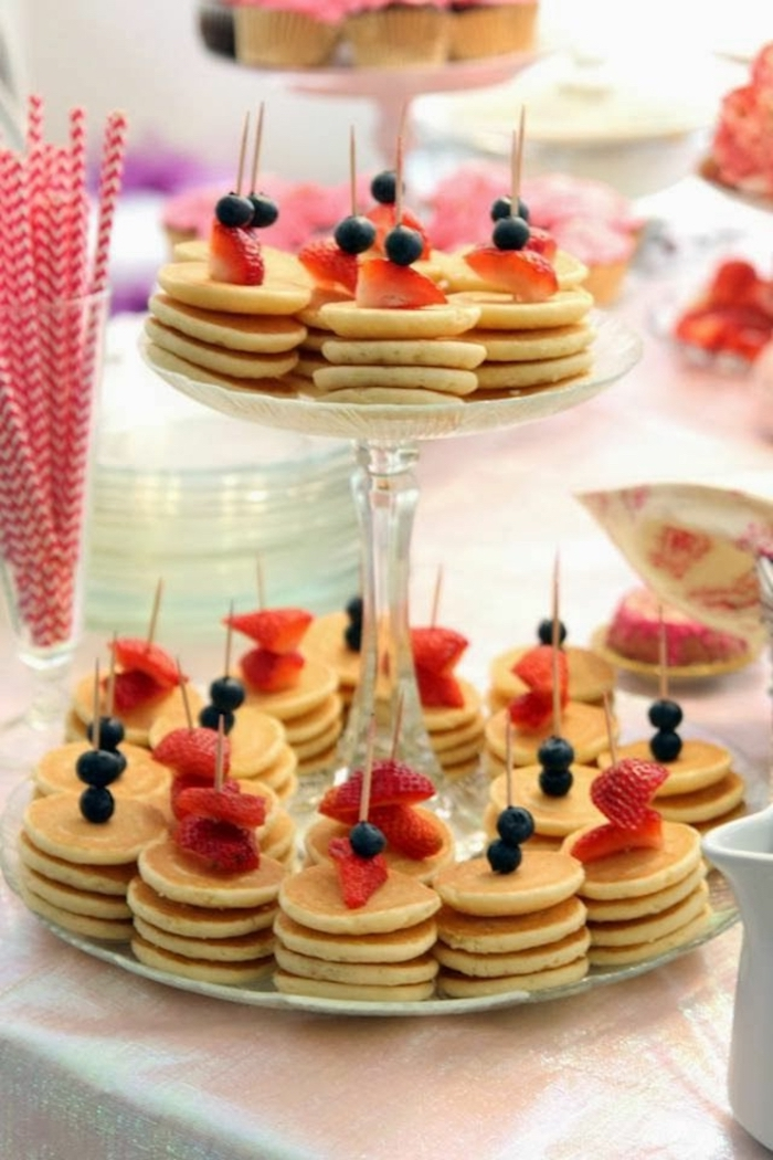 mini pancakes, easy brunch ideas, blueberries and strawberries on top, glass cake stand, paper straws