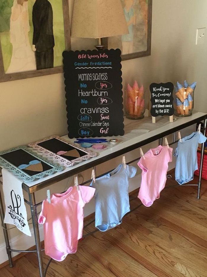 welcome table, pink and blue onesies, gender reveal pinata, old wives tales board