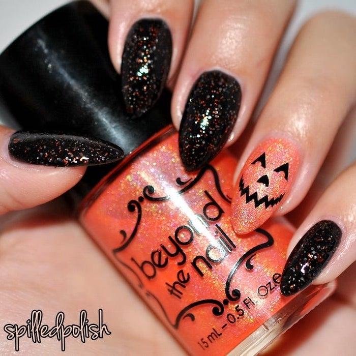 cute acrylic nail ideas, black and orange, glitter nail polish, almond nails, holding an orange glitter nail polish