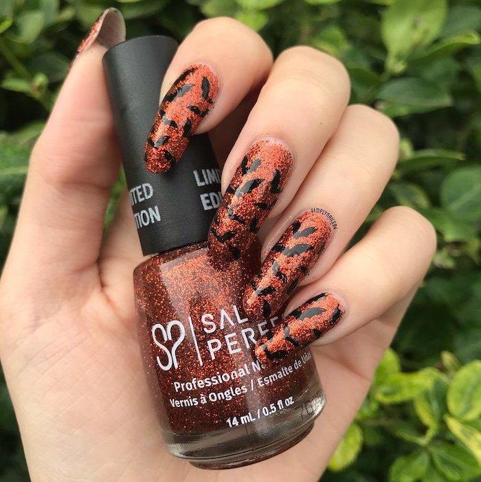orange glitter nail polish, cute halloween nails, long squoval nails, black bats decorations, holding an orange glitter nail polish bottle
