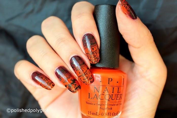 orange nail polish, cute halloween nails, black halloween decorations, holding an orange nail polish bottle