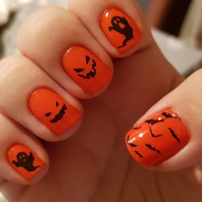 cute halloween nails, orange nail polish, black decorations, ghosts and bats, short squoval nails
