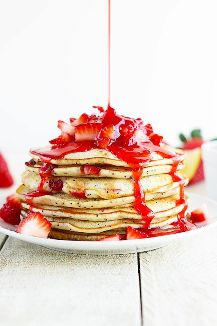 stacks of pancakes, strawberry jam, chopped strawberry, breakfast sides, wooden table