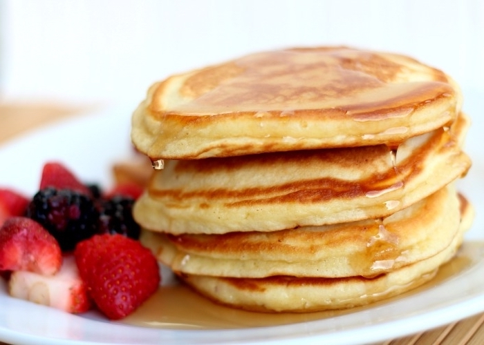 pancakes stack, honey on top, breakfast sides, strawberries and blackberries, white plate