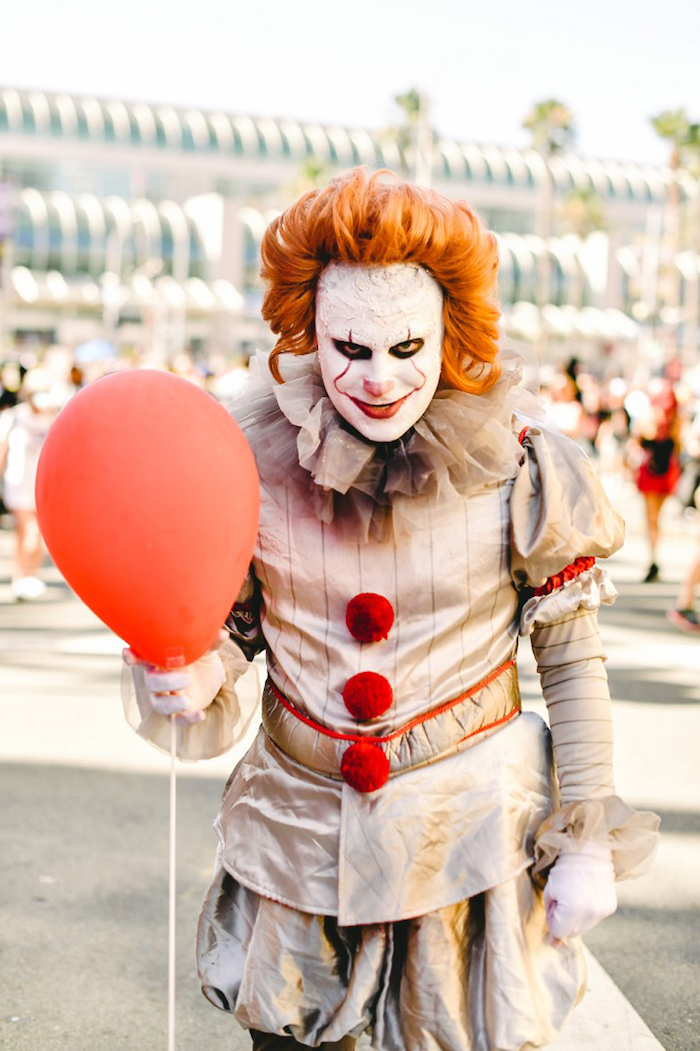 man dressed as pennywise, it movie inspired costume, diy halloween costumes, holding a red balloon