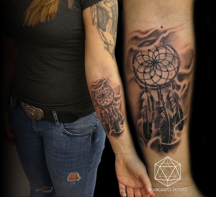 forearm tattoo, dream catcher tattoo on arm, woman with black t shirt, ripped jeans, blonde hair