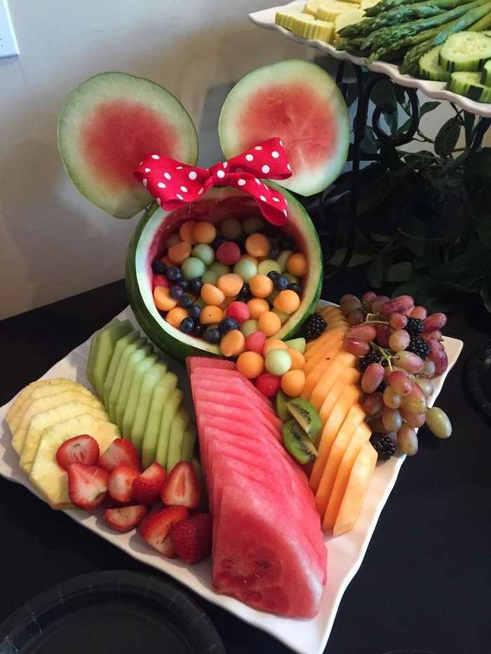 watermelon carved, as minnie mouse, filled with fruit, baby shower themes for girls, sliced fruits, white plate