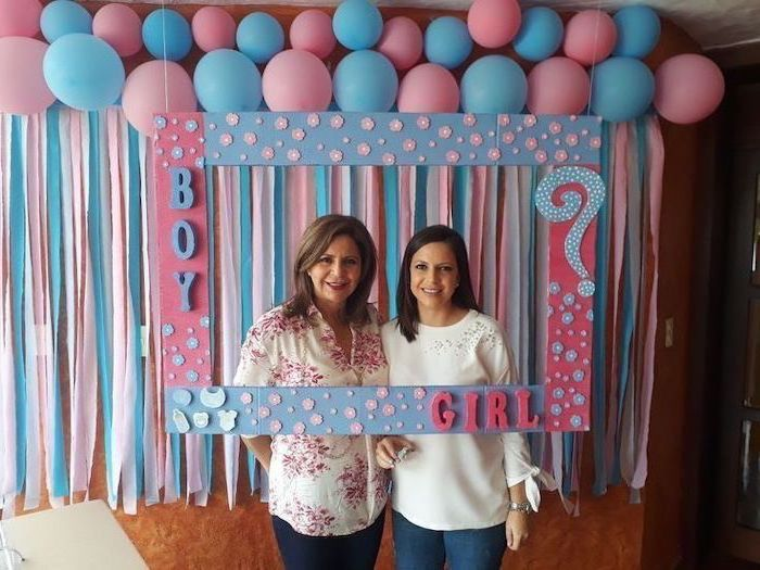 two women smiling, gender reveal pinata, photo frame, in pink and white, lots of balloons