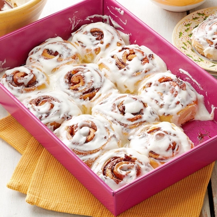 brunch ideas for a crowd, cinnamon buns, with white frosting, in a pink box, yellow cloths