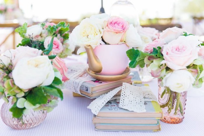 small teapot, flower bouquets inside, on top of books, baby shower table decorations, white ribbons
