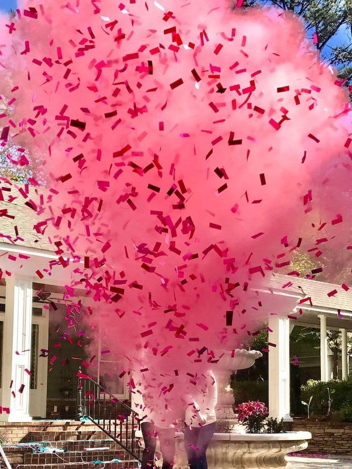 pink smoke, pink confetti, gender reveal games, man and woman standing, in front of a fountain