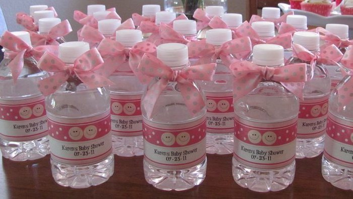 pink and gold baby shower, water bottles, party favors, pink satin ribbons, wooden table