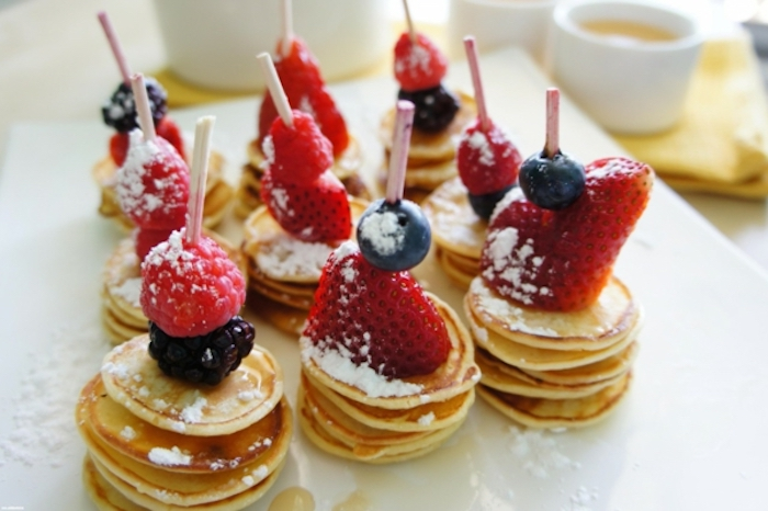 stacks of mini pancakes, brunch ideas for a crowd, raspberries and strawberries, powdered sugar on top