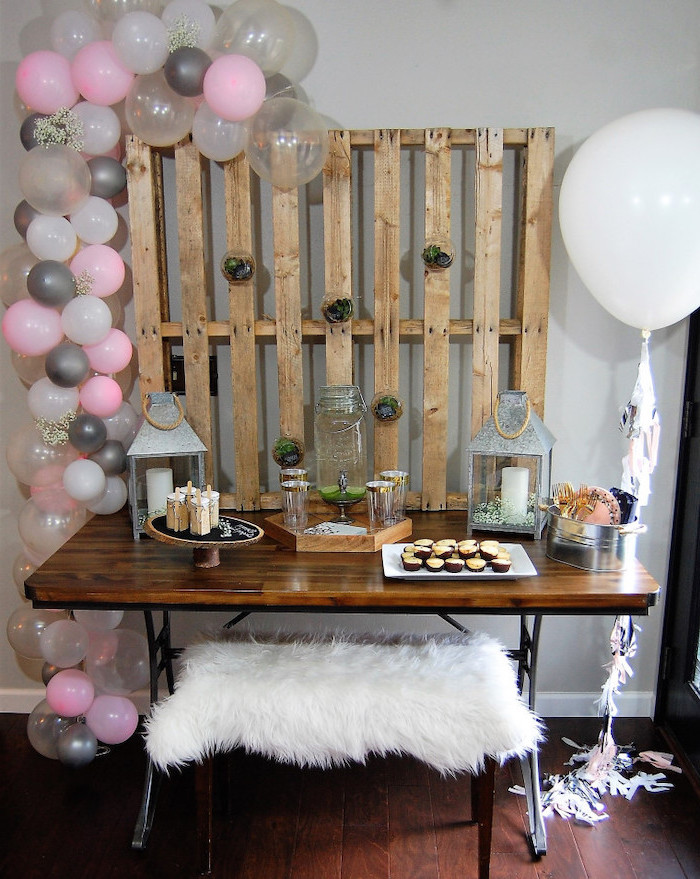 pink white and grey decor, wooden pallet, wooden table, places to have a baby shower, candle lanterns