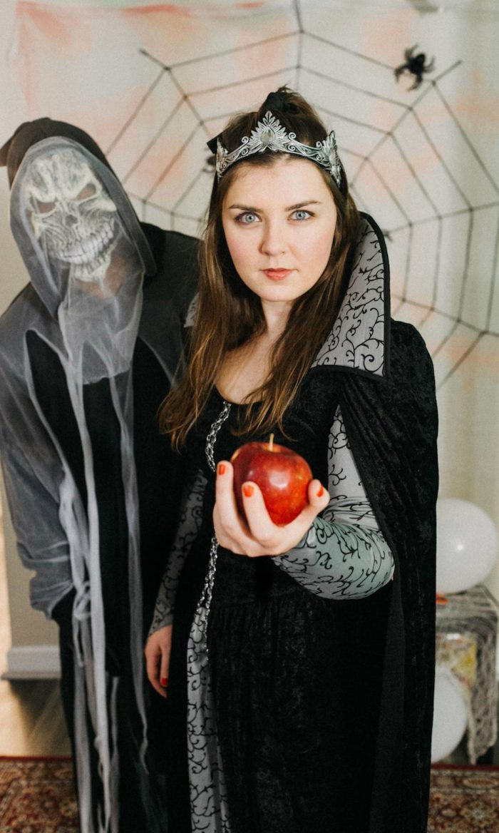man with a skeleton costume, famous halloween characters, woman dressed as the evil queen, holding a red apple