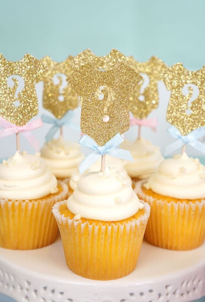 small cupcakes, with white frosting, gold glitter onesies, cake toppers, gender reveal ideas, blue bows