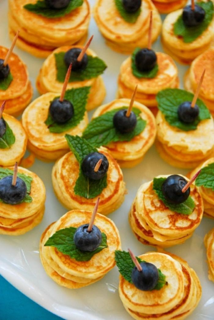 stacks of mini pancakes, fancy breakfast, mint leaves, blueberries on top, white plate
