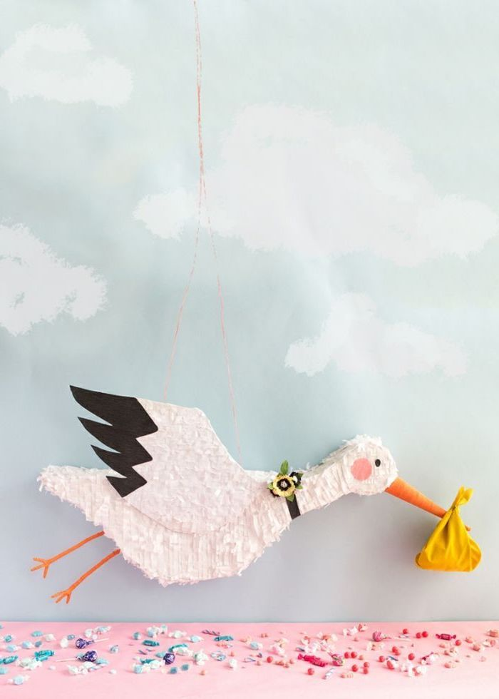 gender reveal ideas for family, pinata in the shape of a stork, candy on the table, blue background