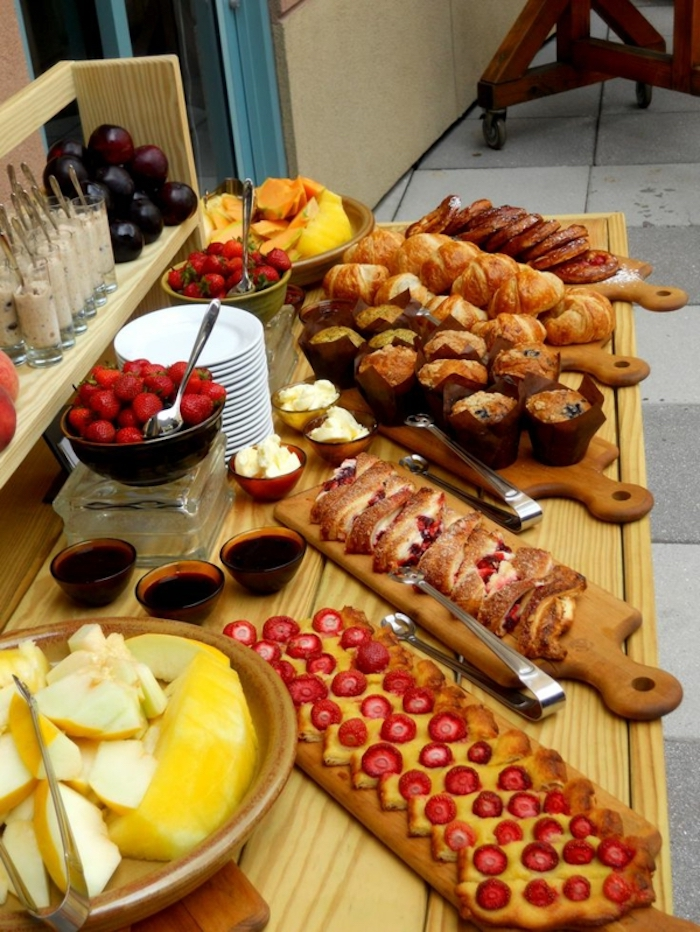 brunch table, fancy breakfast, wooden boards, bowls of different fruits, stack of plates