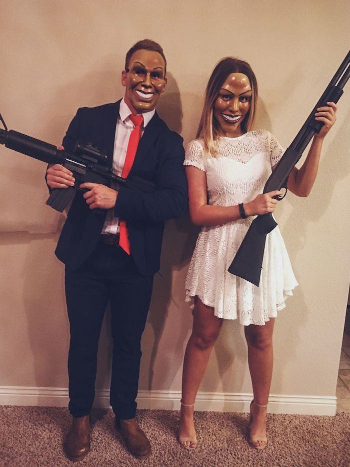 man and woman, dressed as characters from the purge, funny halloween costumes, suit and white dress, holding rifles