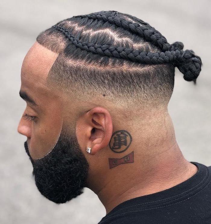 short braids hairstyles, man with black hair, braided in a bun, black beard, black t shirt, neck tattoo