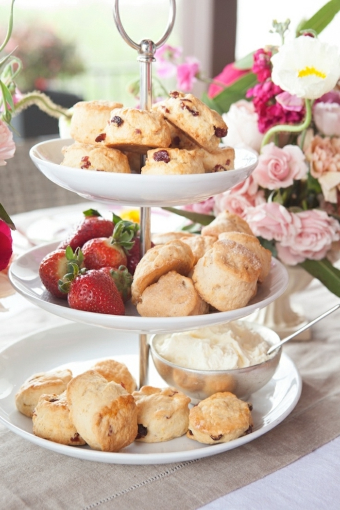 white cake stand, things to make for breakfast, scones and strawberries, cream in a bowl, flower bouquet