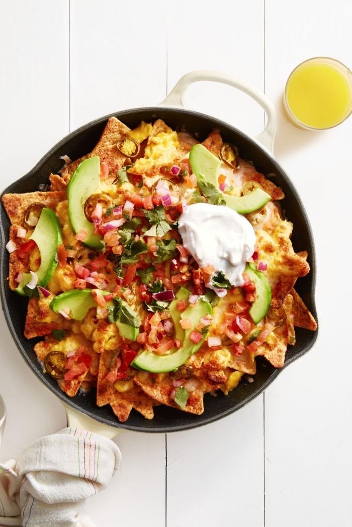 nachos in a pan, vegan brunch recipes, tortilla chips, covered in salsa, avocado sliced, sour cream