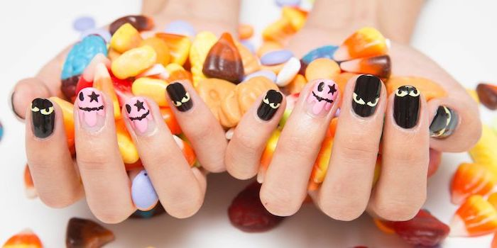 two hands, holding candy, short squoval nails, orange ombre nails, pink and black nail polish