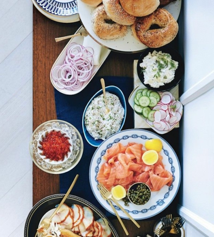 brunch table, chipped onions and cucumbers, salmon fillet, bagels on a plate, different garnish, vegan brunch recipes