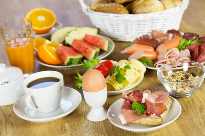 wooden table, basket of bread, coffee and orange juice, vegan brunch recipes, plate of salami and ham