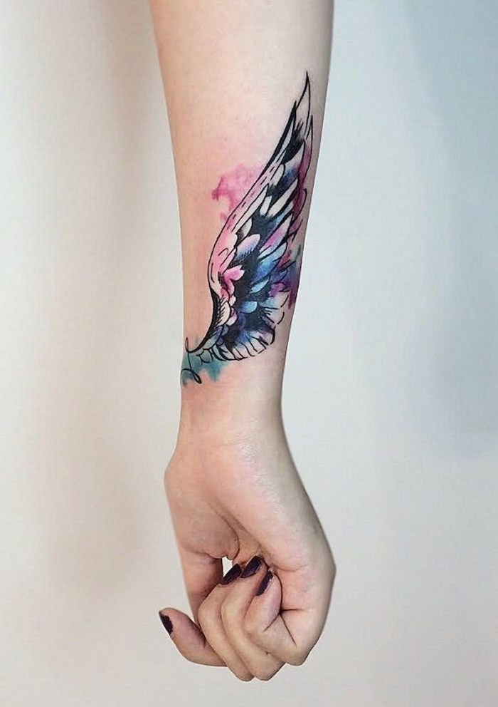 forearm tattoo, watercolor tattoo, wing tattoo on arm, white background, pink and blue colors, black nail polish